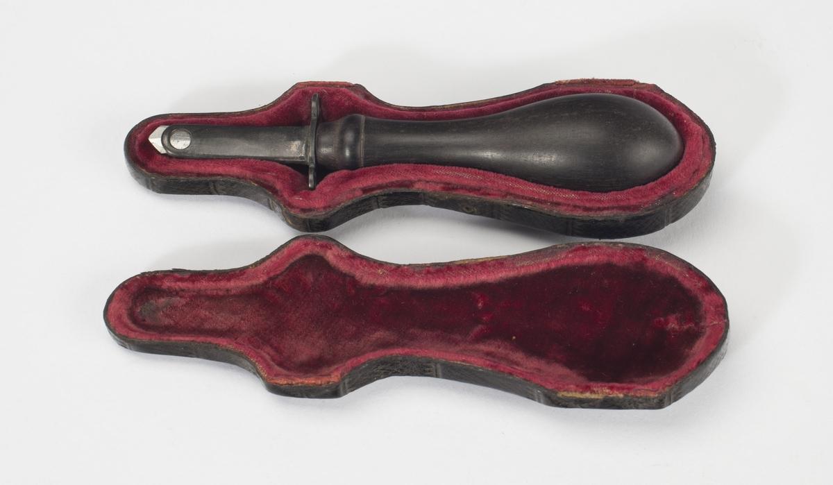 Flat, knivlignende triokar med skjærende V-formet spiss. Har en liten metallslire. Skaft i svartlakkert tre.
