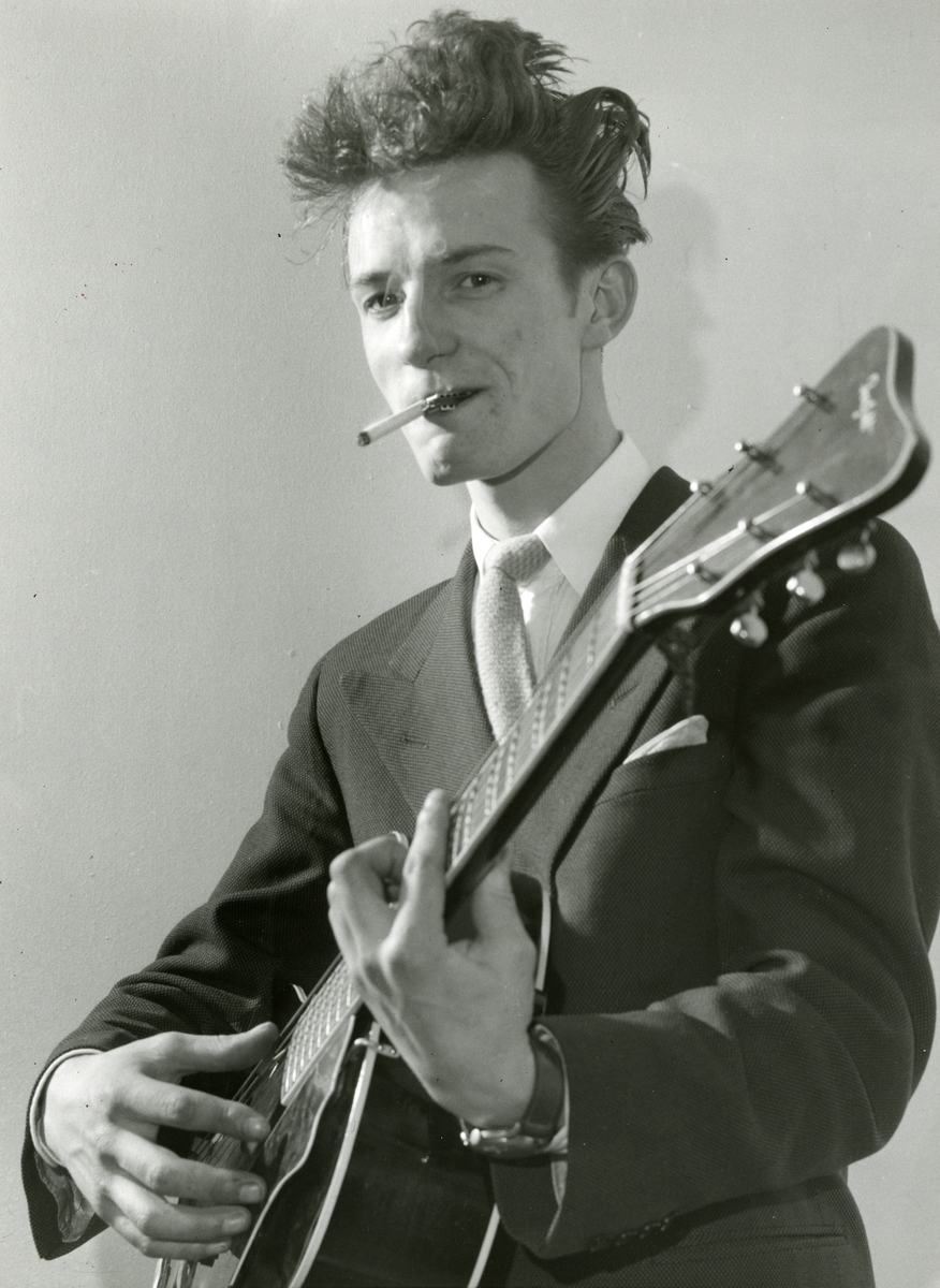 Ung mann med gitar som røyker.
