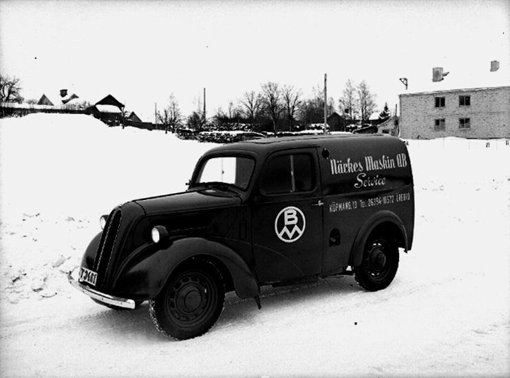 En bil.Närkes Maskin AB, service, Köpmangatan 13, Örebro.Bostadshus och byggnadder i bakgrunden.Vintermotiv.