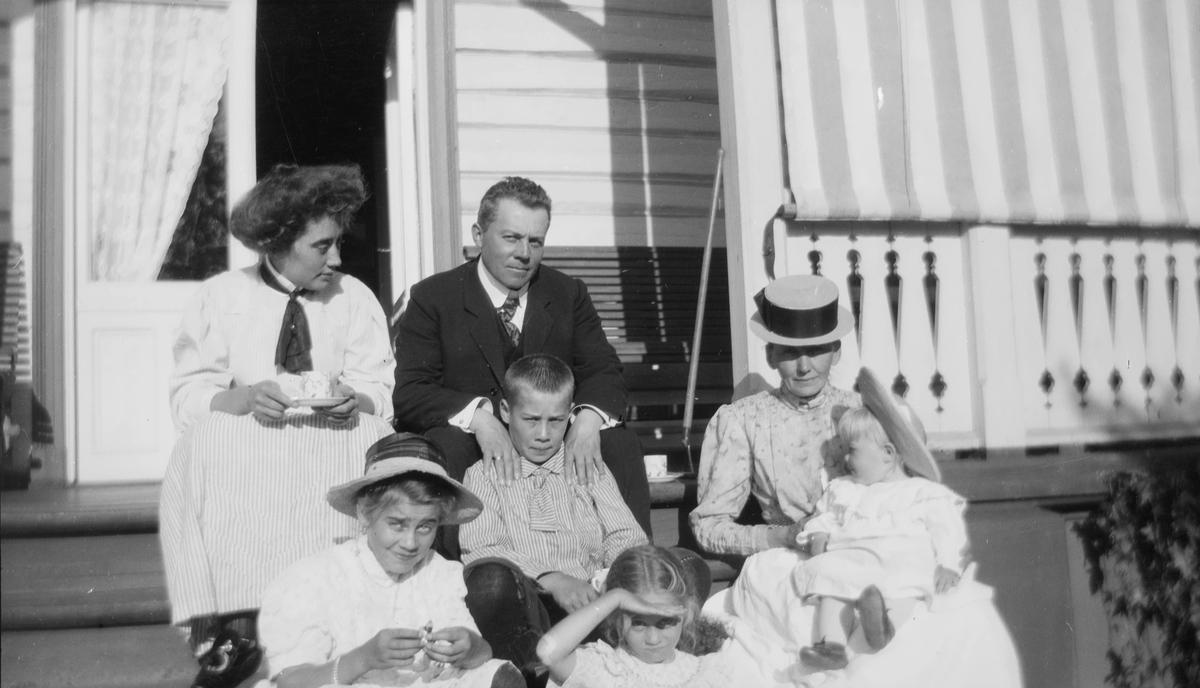 På en verandatrapp sitter: øverst, fra venstre: Celina Ihlen Mathiesen, Christian Pierre Mathiesen og en uidentifisert kvinne. Nederst, fra venstre: Celina marie, Haaken Christian, Ise (Louise) og Iacob Ihlen.
