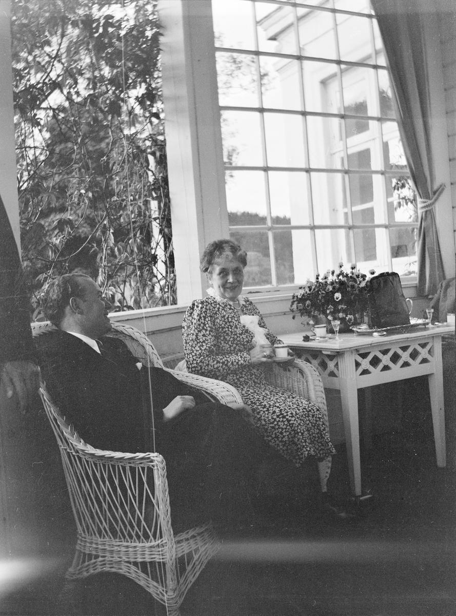 Iacob Ihlen Mathiesen og en eldre kvinne sitter smilende i kurvstoler på verandaen på Linderud Gård.