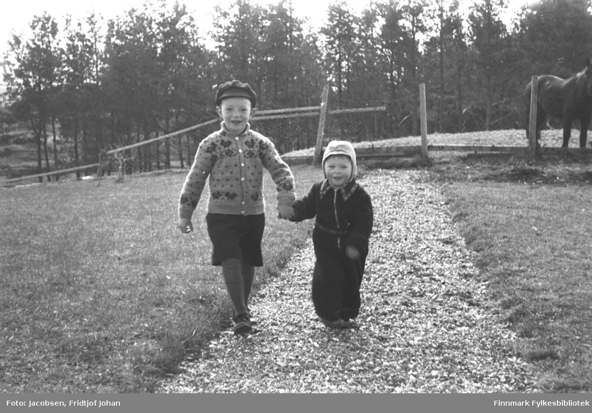 To små barn går på en liten grusvei og leier hverandre. Barnet til venstre på bildet har en stikkejakke, mørke benklær og en skyggelue på hodet. Det mindre barnet har en mørk buksedress og en forholdsvis lys lue på hodet. En gressplen ligger på begge sider av stien. Gjerdestolper med netting i mellom står med jevne mellomrom. Bak til høyre på bildet står en hest og mye løvtrær ses i bakgrunnen. Omgivelsene ser landlige ut