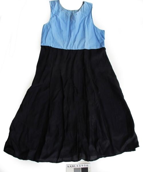 Kjole, foldet skjørt av mørk blå tynnt glatt stoff, med overdel av lys blå bomullstoff.  Løs jakke av samme stoff som skjørtet.  Maskinsøm og håndsøm. Trykknapper i jakken.  Innsydde puter på skuldrene.   a. Kjole  b. Jakke