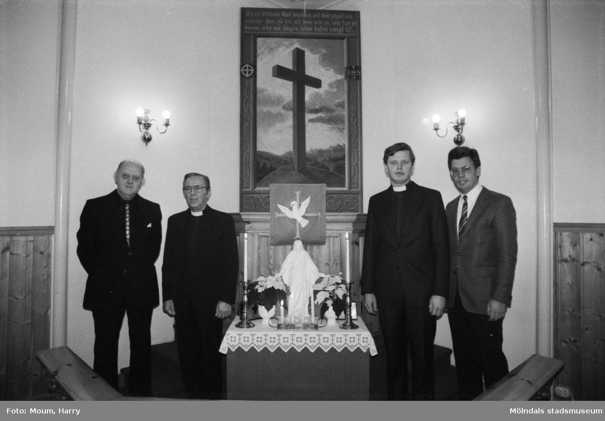 Greggered kapell i Lindome, år 1983. Pastorerna Gustaf Carlstedt och Anders Svensson tillsammans med två andra herrar framför kapellets altartavla.  För mer information om bilden se under tilläggsinformation.