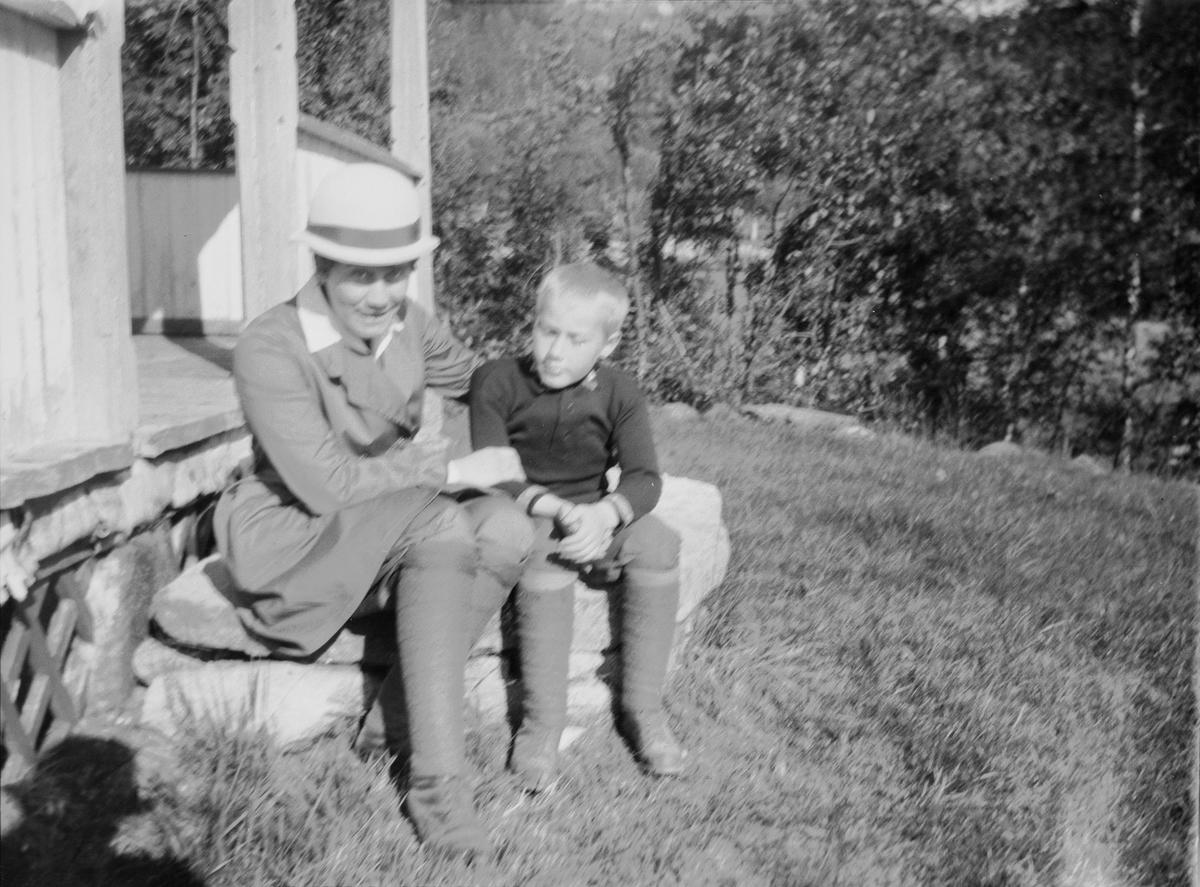 Celina Ihlen Mathiesen sitter på en steintrapp, utenfor en fritidsbolig i Jeppedalen, sammen med en av sønnene.