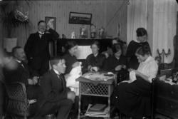 Rumsinteriör, släktgrupp nio personer i hemmet på Kungsgatan
