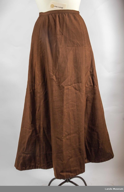 Tøyet er en tynn firskaftet kypert (batavia) i ull. Foret har samme teknikki grå bomull. Skjørtet er helforet og tatt med i sømmene. Alle sømmer er noe skrådd. Midt bak der sømmen ender i en 21 cm lang splitt som lukkes med fire trykknapper. Det er søm i hver side og ved en skrådd bredde midt foran. Linningen er 1,5 cm bred og lukkes med to hekter/maljer. I nederkan er det ca. 8 cm bred skoning (belegg) og i nederkant er det sydd fast et makinvevd bånd (støvkant) med plysjkant som vises nedenfor skjørtekanten og ellerr ca 1 cm lerretsvev for festing. Båndet er svart.