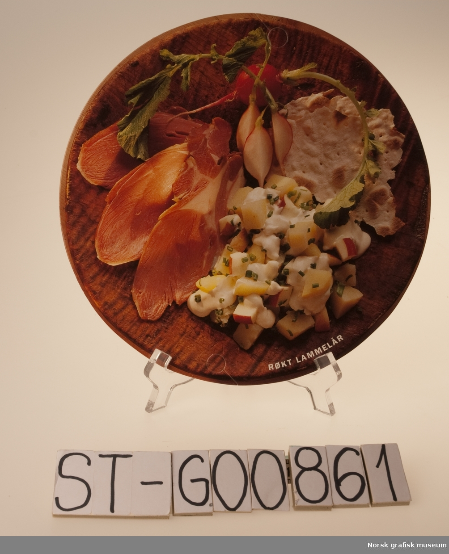 """4 runde """"plakater"""" utformet som tallerkener med mat på.  Motiv: Reinsdyrstek, Røkt Lammelår, Lammerull, Pinnekjøtt, syltelabber, Juleskinke, Paté og Ribbe, Medisterkaker og -pølse  Språk: Norsk"""