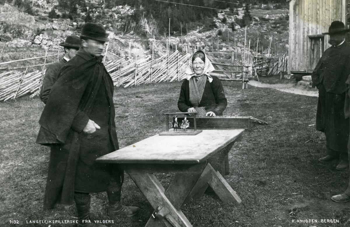 Berit på Pynten står ute på et gårdstun sammen med tre menn. Hun spiller på en langeleik som ligger på et bord.