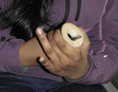 Hender som skjærer ut en ring i tre med tollekniv.