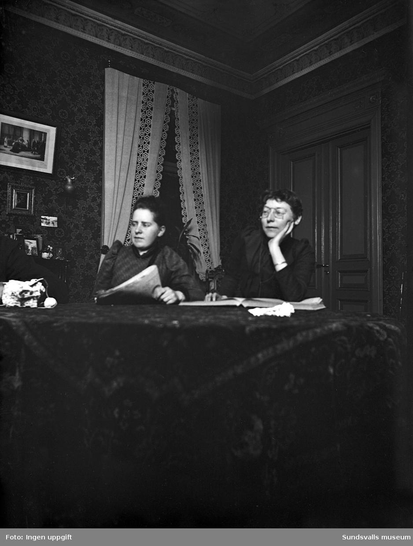 Två kvinnor läser tidningar i rumsmiljö.