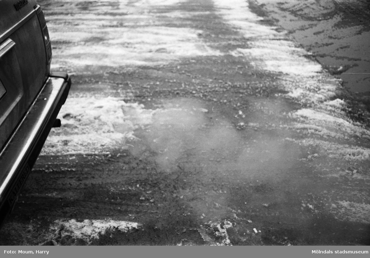 Bil släpper ut avgaser i Kållered, år 1984.  För mer information om bilden se under tilläggsinformation.