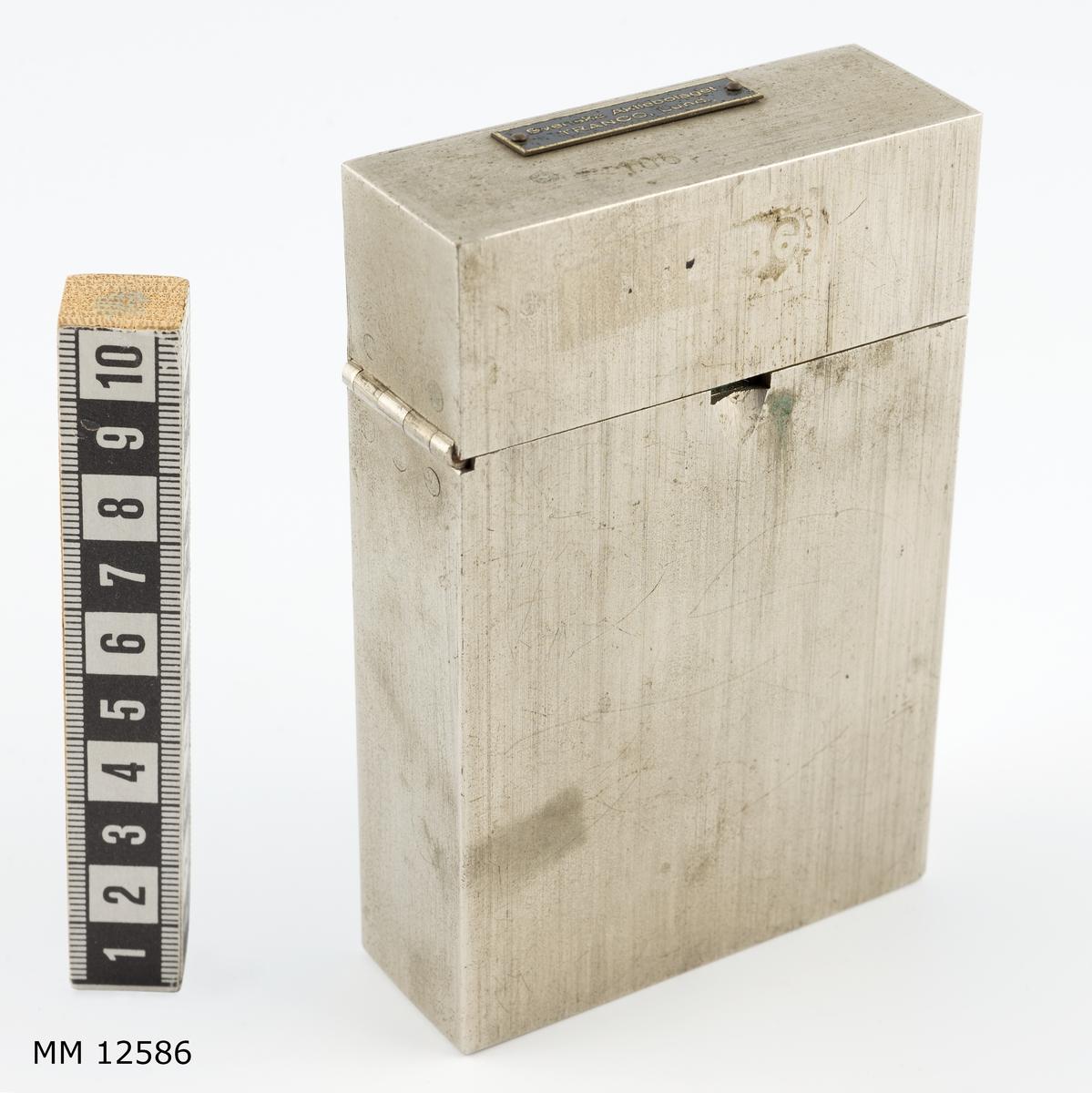 Består av ett fodral av metall med löst insatt plåtställning. På denna en tub med indikeringspapper och el.glödlampa med torrbatteri. I fodralets lock en tub med indikeringsvätska.