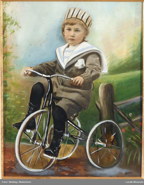 portrett av gutt som 3-4-åring på trehjul-sykkel iført strikkedress med matroskrave,hatt og svarte støvler