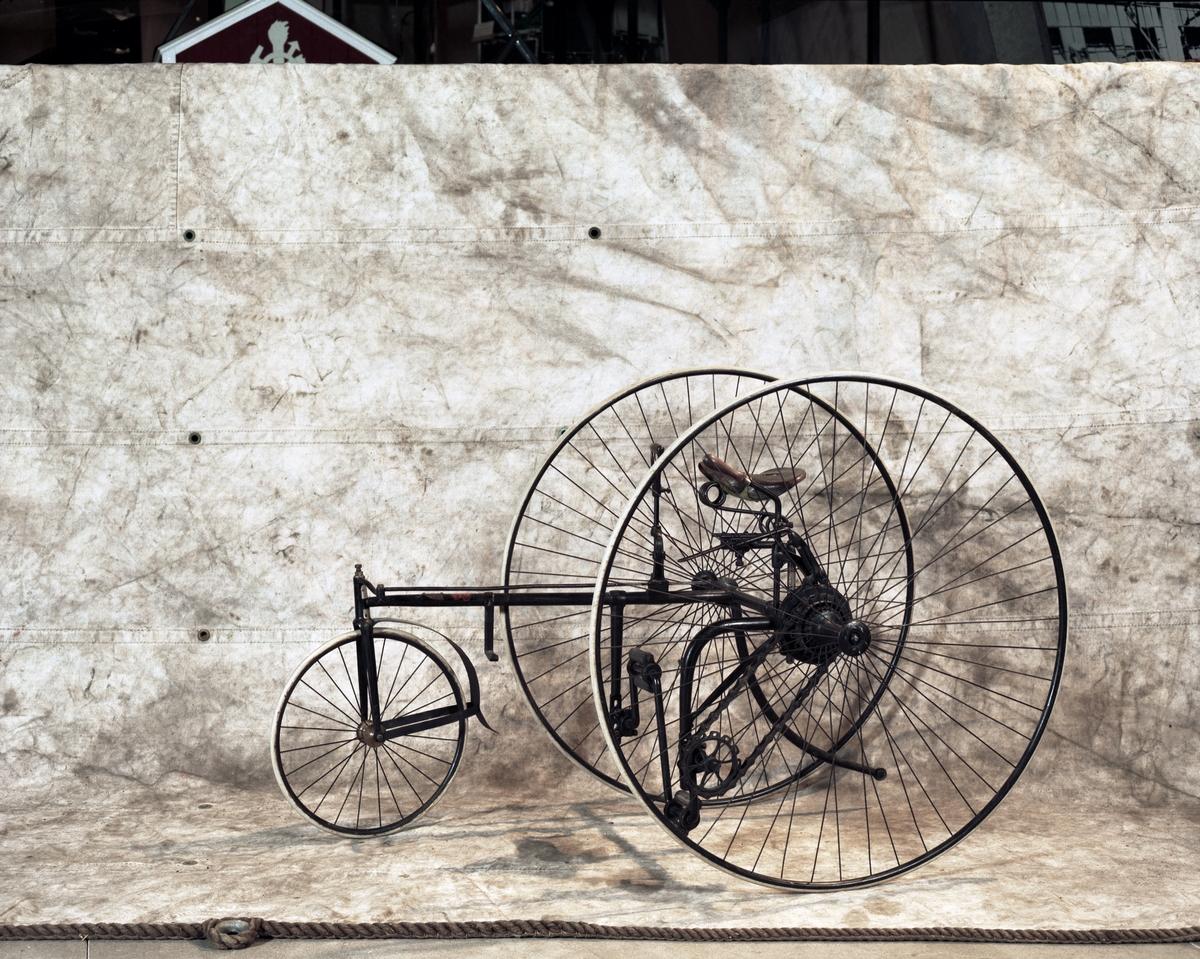"""Trehjulig cykel. Styrning med högerhandshandtag som påverkar kugghjul-kuggstång. Bromshandtag för vänsterhand. Kedjedrift. Två stora bakhjul, ett litet framhjul och """"damsadel"""", vilken är mycket trasig. Massiva däck. Märkning: The Royal Mail Tricycle, på sköld av mässing. Röd dekal: The Royal Machine Manufacturing Co Ltd, Birmingham."""