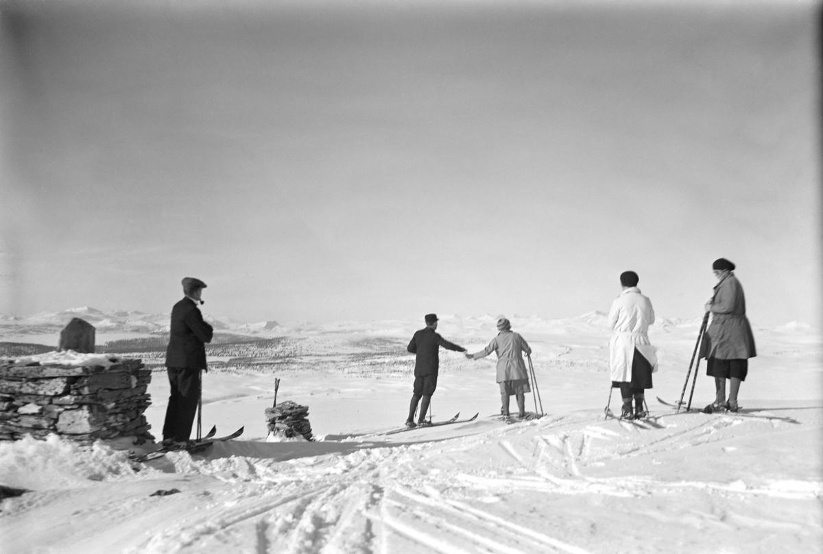 Øksendalskampen. Fem personer på ski. Tre damer med skjørt og to  menn