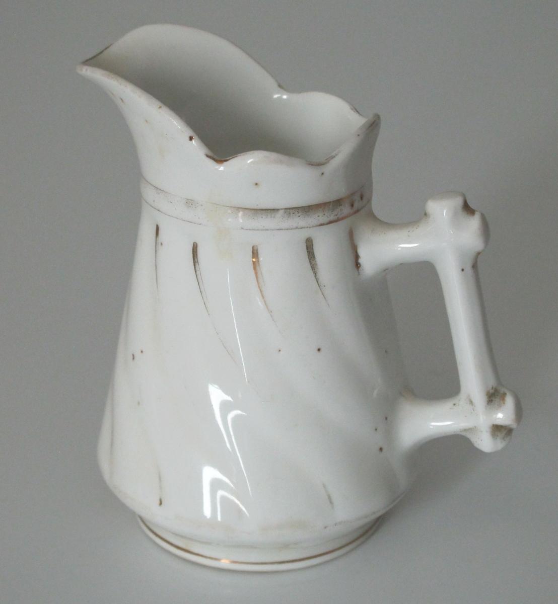 """Fløtemugge av porselen, hvit glasur med avslitt gull. Skrå sider med svungne riller med gullstriper.  Tuniet kontur øverst og bred tut. """"Laftet"""" hank."""