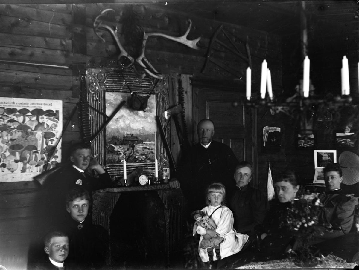 Mennesker i interiør. Maleri, peis, plakat over sopp, jakttrofeer og jaktutstyr. Jente med dukke