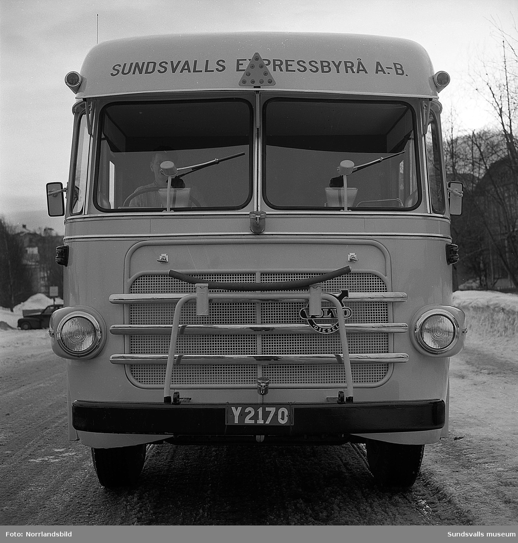 Sundsvalls Expressbyrå AB. Möbeltransportbuss fotograferad på Parkgatan. De båda träkåkarna i bakgrunden är numera rivna.