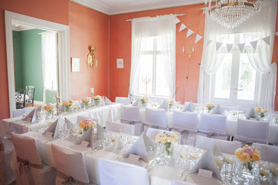 Stue med hesteskoformet bord dekket til bryllupsmiddag.