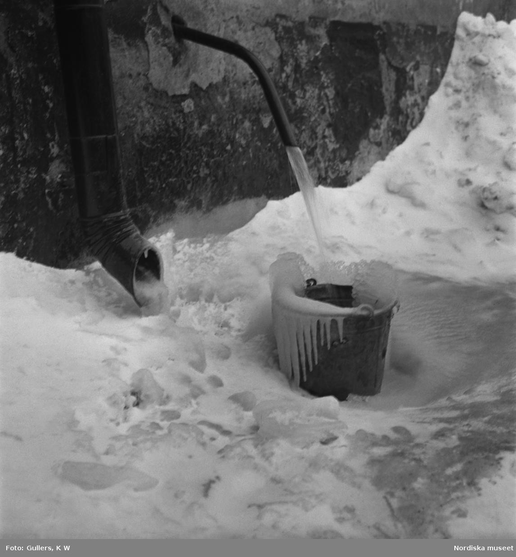 """Inne på en gård står en överisad hink med skvalande vatten från en kran. """"'Låt vattnet rinna!"""" står det på ett klumpigt textat anslag ovanför den överisade pumpen.'"""""""