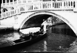 Drottning Victoria bilder. Man i gondol under bro i Venedig.