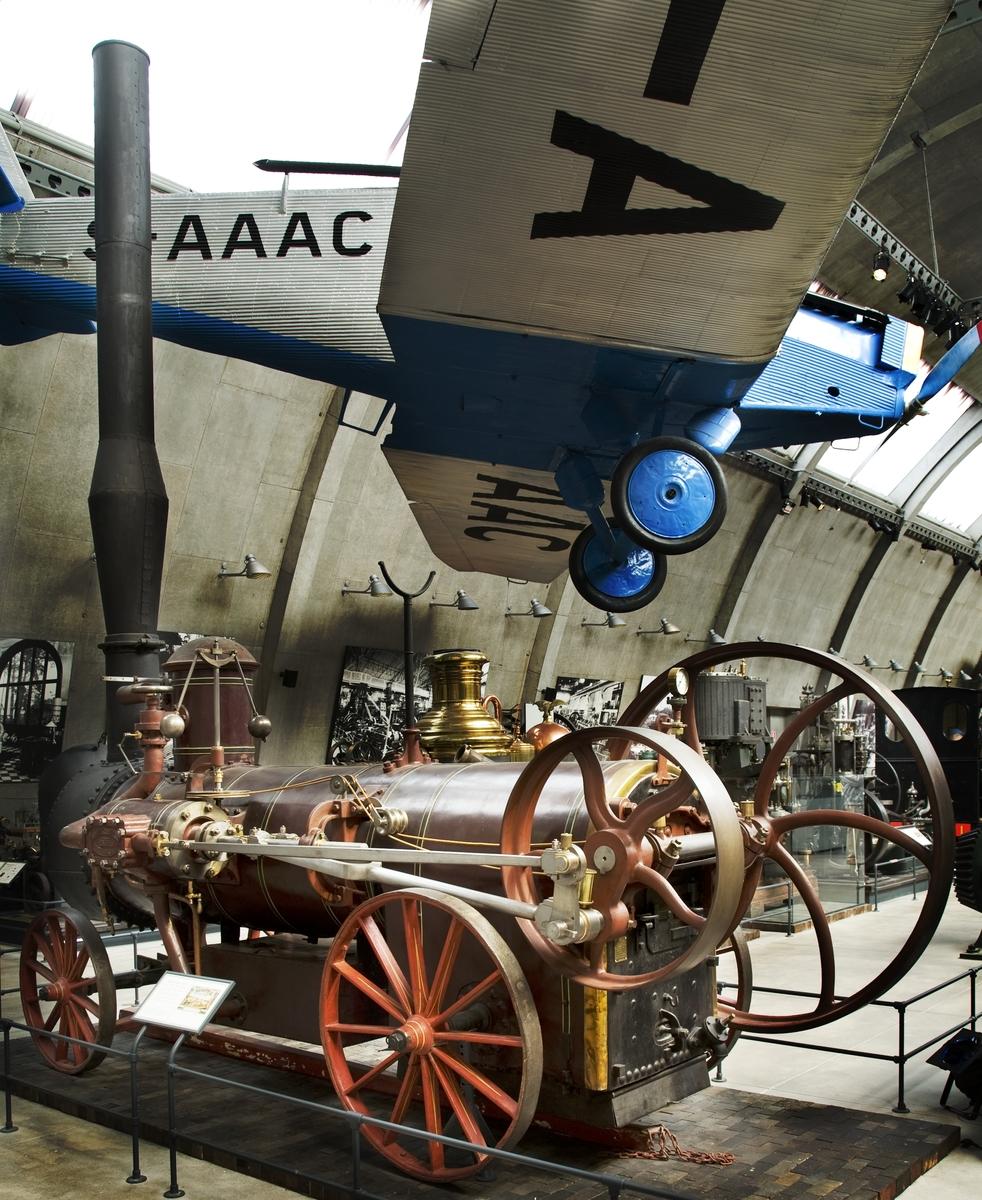 Lolomobil på fyra hjul, avsedd att dras av parhästar. Tillverkad enligt Th. Munktells patent. Den har en lokomotivpanna, d.v.s. en panna med fyrbox i ena ändan och liggande rökgastuber. Tuberna sträcker sig från fyrboxen till sotskåpet i pannans ände. Fällbar skorsten med s.k. gnistsläckare. Lådformad matarvattentank under  pannan.  Encylindrig, dubbelverkande. Cylindern är monterad på pannans ena sida. Kolvstången saknar tvärstycke men går genom en yttre stödlagerhylsa. Remdriven centrifugalregulator. Utblåsning av ångan sker genom en rörslinga i matarvattentanken. Ger 8 hk vid ångtrycket 4,5 bar (klassad till 10 Nhk). Tillbehör: Lösa delar: (skorsten), stång, två st. svänglar samt stödgaffel för skorsten.