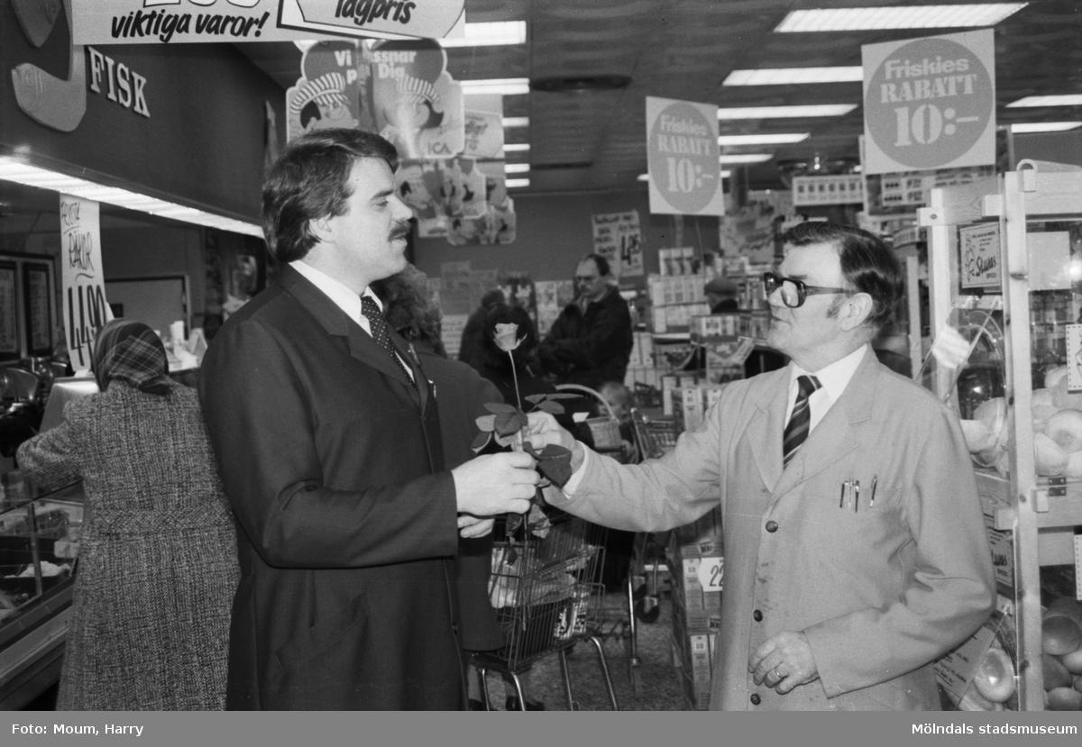 """Olle Eriksson och Werner Fasnacht i livsmedelsaffären Almåsboden i Lindome, år 1984. """"""""Olle i Lindome"""" sade tack och farväl med en ros till varje kund och efterträdaren Werner Fasnacht (t v) fick också en.""""  För mer information om bilden se under tilläggsinformation."""