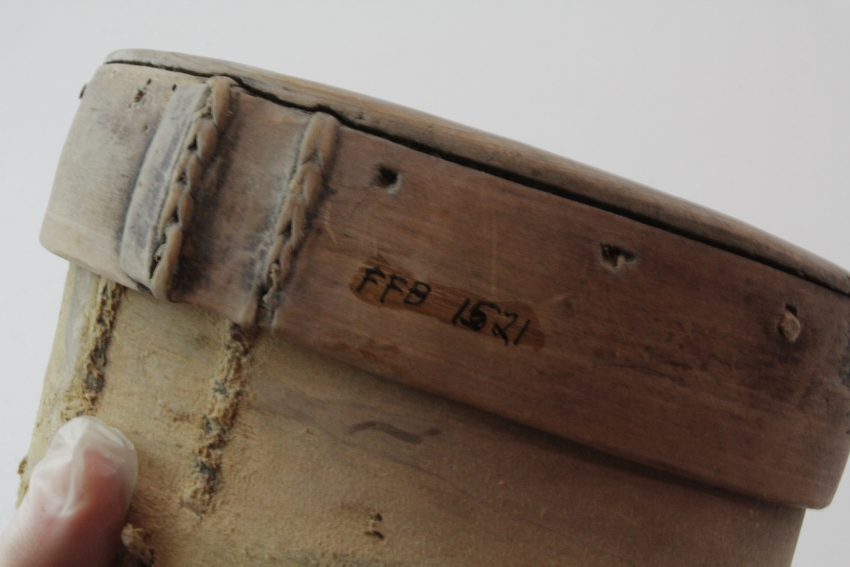 Oval øskje laget av spaltet tre og sydd sammen med teger i siden. Ovalt lokk der siden er sydd sammen mens toppen er klinket fas med trenagler.