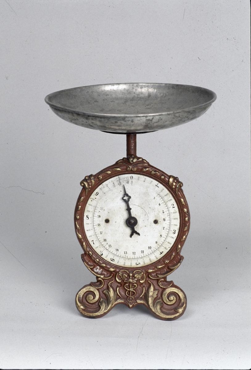 Fjädervåg för 0-25 skålpund och 0-10 kg, på fundament av gjutjärn. Ornament i guldbrons. Skål av förtent järnplåt.