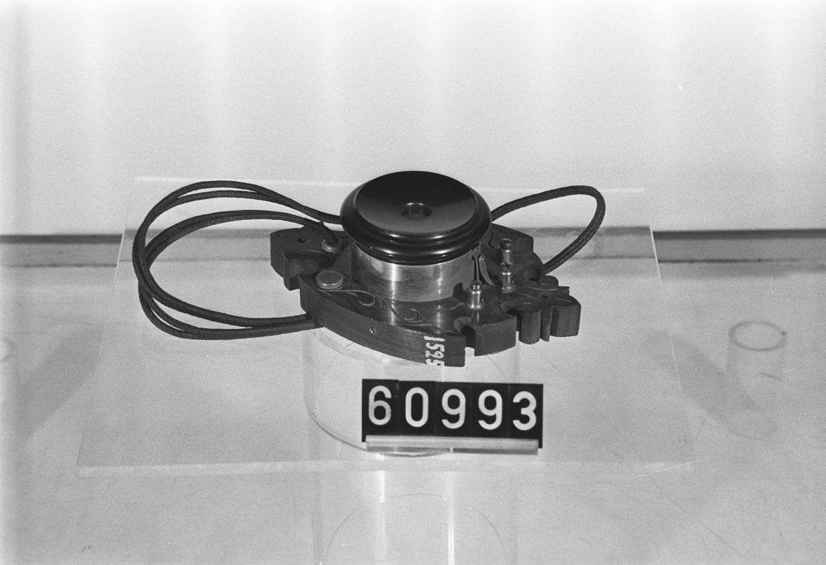Telefonapparat, galvanisk rumstelefon, på sköldformad träplint. En bland de minsta väggtelefoner som (vid tiden) tillverkats.
