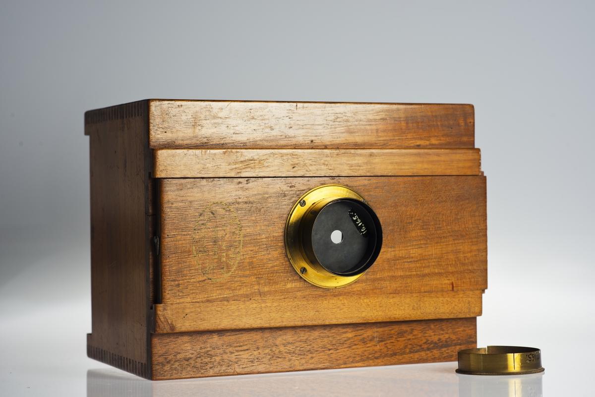 """Lådkamera för experiment med stereoskopbilder, genom ett i sidled förskjutbart objektiv, bildformat 8,5 x 8,5. Tryckt: """"I. Binhof Lehrmittel-Anstalt Berlin N"""". Tillbehör: Visirskiva, 2 st. hålbländare, ringhållare för bländarna och objektivlock samt stativ med klämskruv för olika lutning."""