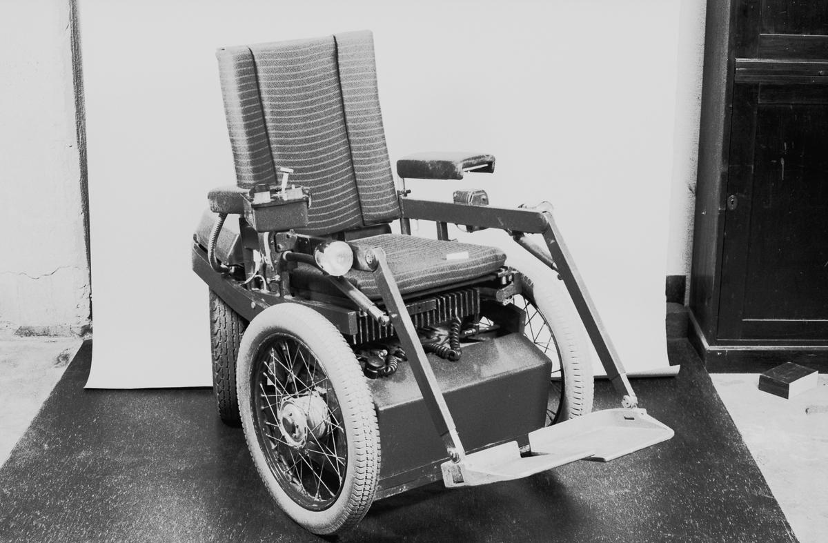"""Eldriven rullstol. Fart 10-15 km/tim. Tar stigningar på 40 %. Markfrigång 15 cm. 180 grader vridbara bakhjul med lufttryck 0.3-0.8 kg. Drivmotor: Hägglunds likströms MOT-SERIE, Typ: ML 0,25 , Nr: 1004951, 0,38kw kont, 1900r/m, 24V, 25A. Snäckväxel: Typ: 400-202, Nr: 3627, Utv: 36:1, Hk: 1,2 , Ing.v:1400, Utg.v:39. Detalj på snäckväxeln märkt:"""" Aromag P13, Kom 361593, Typ: NAA 0,2 , Spule 36V = 53,5 ohm""""."""