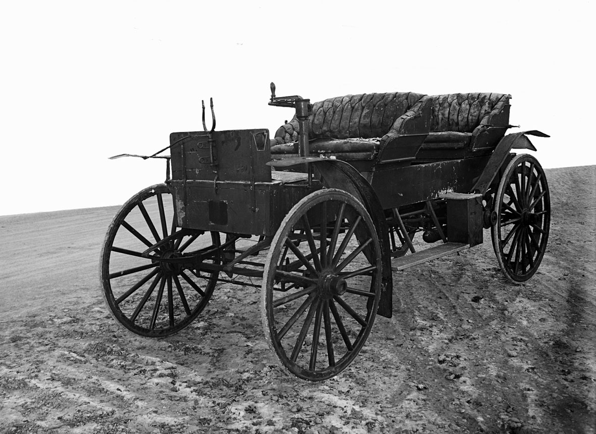 Liggande luftkyld motor med motorblock gjutet vid Överums bruk. Motorn är förskjutbar i vagnens längdsriktning. Kedjedrivning på bakhjulen vid gång framåt, två drivrullar monterade på motoraxeln sköts vid backgång mot de homogena gummidäcken. Styrning med horisontell spak. Kaross tillverkad av Skaftekulla vagnfabrik, Almvik (Hallingebergs sn). Fyrsitsig men bakre sätet är borttagbart för att ge lastutrymme.   Fyrcylindrig bensinmotor Effekt cirka 20 hk vid 1 500 varv/minut