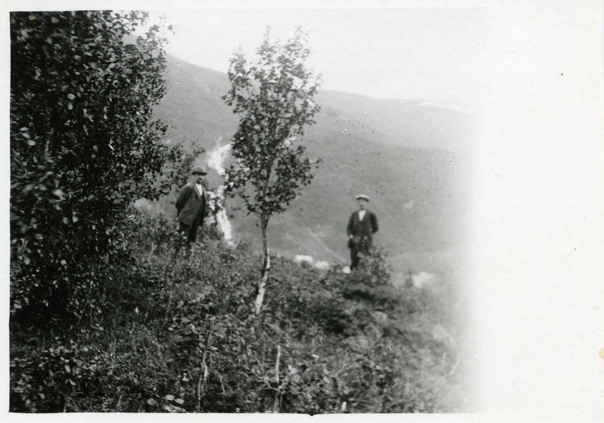 To dresskledde menn står ute i naturen men ei bjørk mellom seg. Det ser ut som ei elv renner nedover ei skogkledd dal-/fjellsiden bak dem.