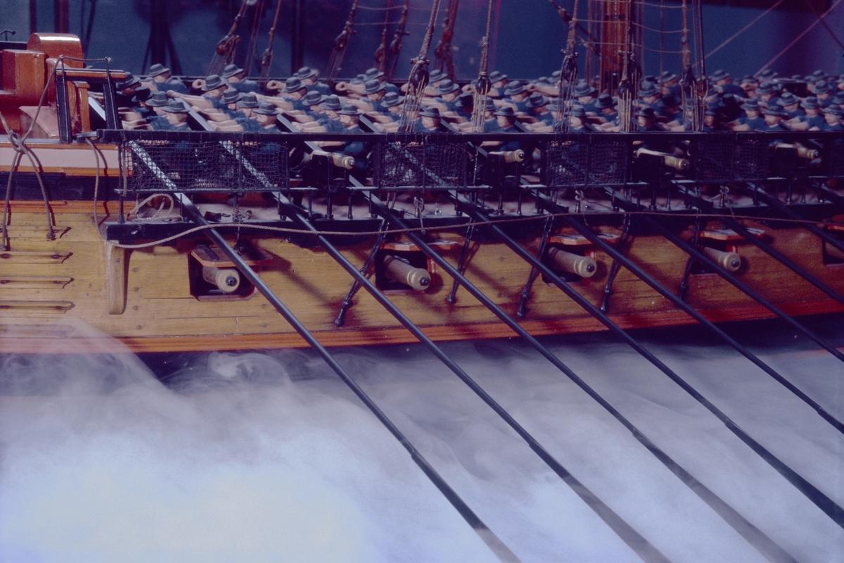 """Fartygsmodell, skärgårdsfregatt, turuma Lodbrok, Chapman konstruktion. Tremastad, riggad utan segel med blå flagg och vimpel. 19 par årtullar. 20 st åror. 2 st bärlingar. Bordläggning på spant med däcksinredning, skulpterad, rödmålad akterspegel med namnet """"Lodbrok"""" samt kartuscher, en med vasakärve och två med stjärnstrålar. Galjonsfigur, röd. Fernissad med svart och rött berghult. Bastingage svart. Rår och toppar svarta. Däcksbyggnader röda. 52 kanoner av förgyllt trä. Kompletterad och restaurerad."""