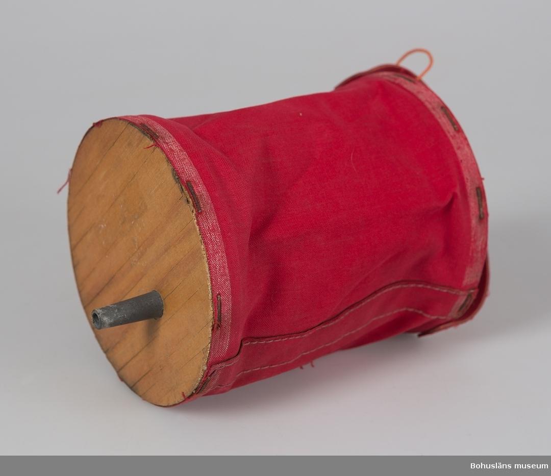 """Luftpump av rött kanvastyg. Två  rundlar av plywood förbundna med ett tygrör fästat med häftklamrar. Den ena rundeln med lufthål och remhandtag. På andra rundeln ett smalt metallrör.  Saknar ABC-märkning. Används för att blåsa upp luftmadtrass med.  För ytterligare upplysningar om  insamlingen, utställningen 2001 och litteratur, se UM027670.  Se exempel på varukataloger i Enskilda Arkiv.  Litteratur: """"ABC-boken nr 82. Huvudkatalog sommaren 1956. Göteborg 1956.  Nordström, Thure. """"...att jobba te Claessons. En bok om ABC-fabrikerna."""" Kungälv 1990."""