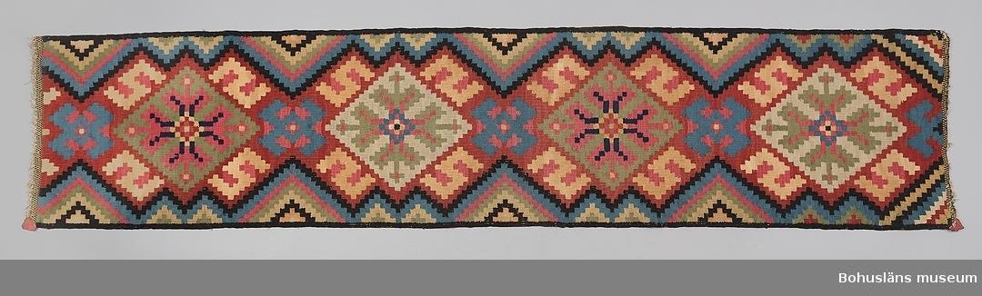 """Bohuslänsk vävnad från tidigt 1800-tal. Vävd i röllakanteknik av växtfärgat ullgarn samt bomullsgarn på linnevarp. Färgerna är rött, svart, ljusgrönt, mellanblått och ljusgult. Den ljusgula nyansen är garn av bomull som ursprungligen varit vit. Det geometriska mönstret uppträder mot en röd botten mönstrad med stiliserade liljor sammanställda i ett likarmat kors, (s.k. liljekors) inskrivet i en romb. Kring varje romb finns fyra gulvita S-former, uppbyggda av små rutor. Mellan romberna mindre blå motiv av romber med fyra """"ben"""". Trianglar i två storlekar, uppbyggda av diagonala linjer i flera färger, sticker in från långsidorna mellan motiven. Långsidorna avslutade med en ram i svart. I ändarna avslutas varpen med inslagsrips och knutar. Vävnadens fyra hörn har ursprungligen dekorerats med kvadrater av klippt rött och blått ulltyg i fem lager. Dessa är bevarade i två av hörnen.  En fastsydd tyglapp på vävnadens undersida anger vävnadens proveniens: """"Denna vävnad i rödlakan (bänkdyna) inköptes  1 september 1921 av undertecknad av hemmansägaren  Adle Johansson Nolby Solberga sn. i Bohuslän. Rödlakans vävnaden uppgavs vara vävd 1809-1810 av A. Johanssons  farmor. Inköpspris 100 kr.  År 1921  Folke Jonasson""""  Enligt litteraturen finns liljan som huvudform i Bohuslän, södra Västergötland och västra Småland, """"genombrutna S-former"""" (uppbyggda av rutor) syns inte som typ utanför Bohuslän.  Inga rester av fjäder eller annat stoppningsmaterial på vävnadens baksida. Färgerna har blekts på framsidan."""