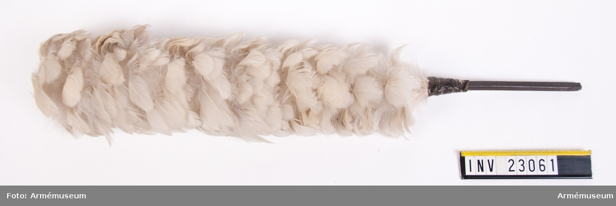 Grupp C I. Ur paraduniform för manskap vid Svea livgarde, 1816-1835. Består av frack, långbyxor, epåletter, björnskinnsmössa, plym, halsduk, patronkök, bandolärrem, axelgehäng, huggarhandrem, skor. Vit fjäderplym. I fodral av papp, med lock. Text på fodralet: Plym, vit, till björnskinnsmössa Svea Livgarde
