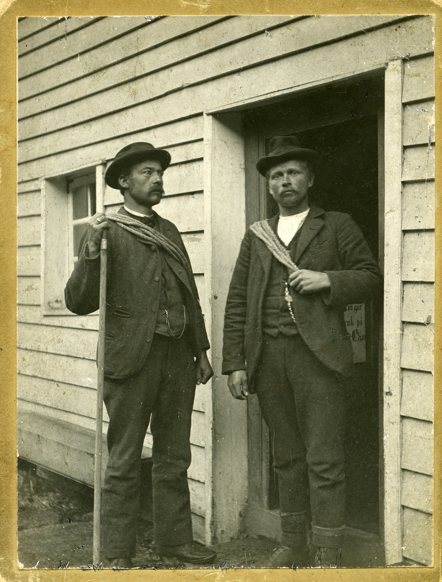 To menn foran en dør. Begge mennene har tau rundt overkroppen og en av dem holder en stokk i den ene hånden.