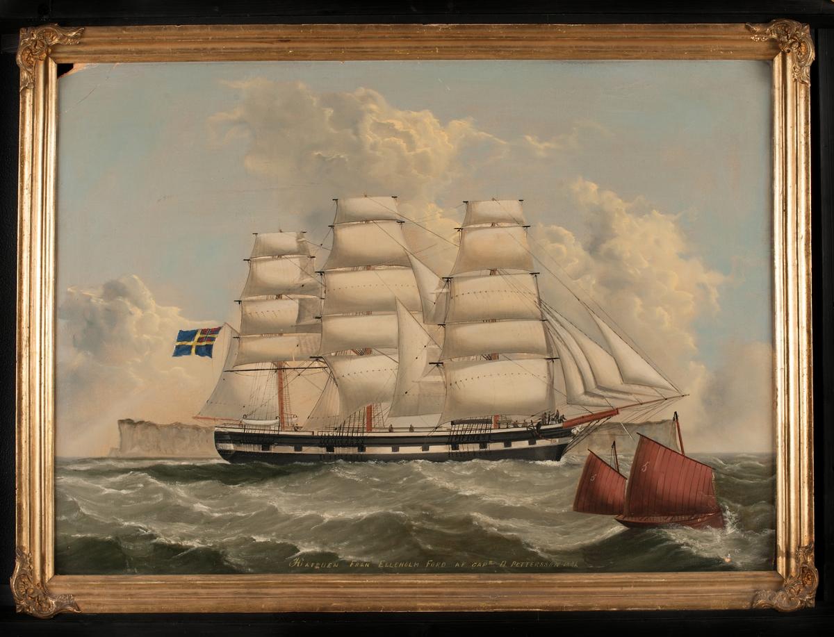 """Fullriggaren """"HAFRUEN från Elleholm. Fartyget ligger för babords halsar, visande läsida, förande alla segel. Svensk flagg med unionsmärke under gaffeln. Skrovet svart med portmålning."""