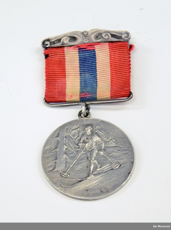 Medalje med innskrift på baksiden: NSF FYLKESREND - DE INTERESSERTES LAGSPOKAL 20-3-26 Bånd i det norske flaggets farger - noe falmet. Stempel på medaljen: 830 S. På forsiden - en skiløper.