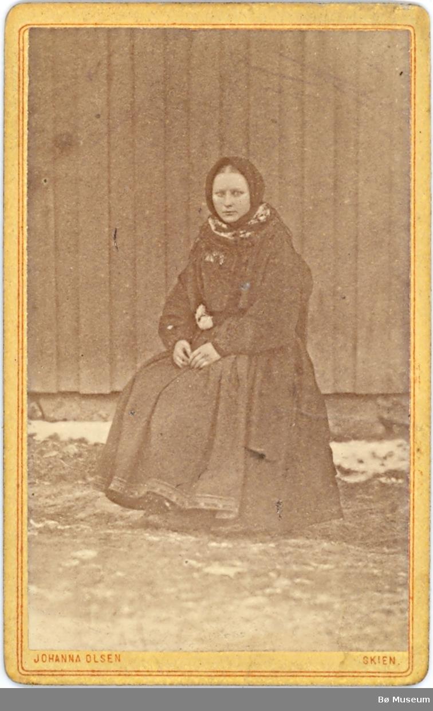 Ukjent kvinne i beltestakk fotografert sitjande ute ved ein husvegg.