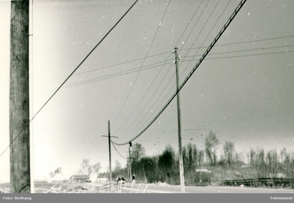 Linjekurser med luftkabel ved riksvegen litt syd for Ottestad sentral, sentralen i bakgrunnen, ca 1960