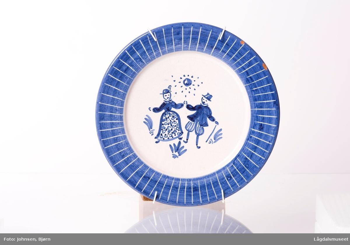 Motivet viser en gutt og jente, mann og kone, under strålende sol. Malt i blått på hvit bakgrunn.