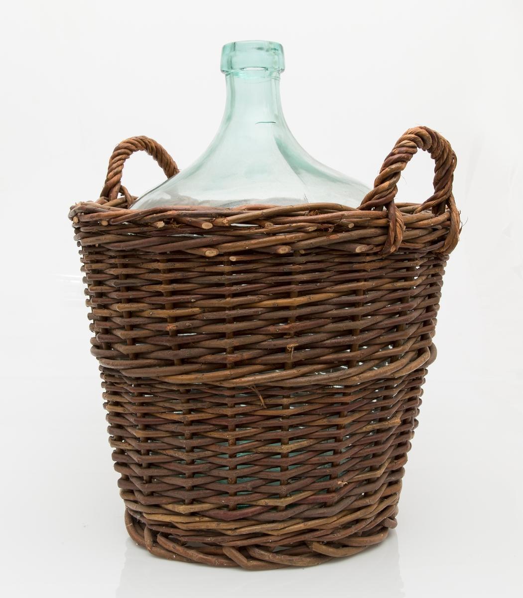 Vinanker plassert i en flettet kurv av pil. Kurven har to håndtak. Vinankeret smalner nederst, mangler kork.