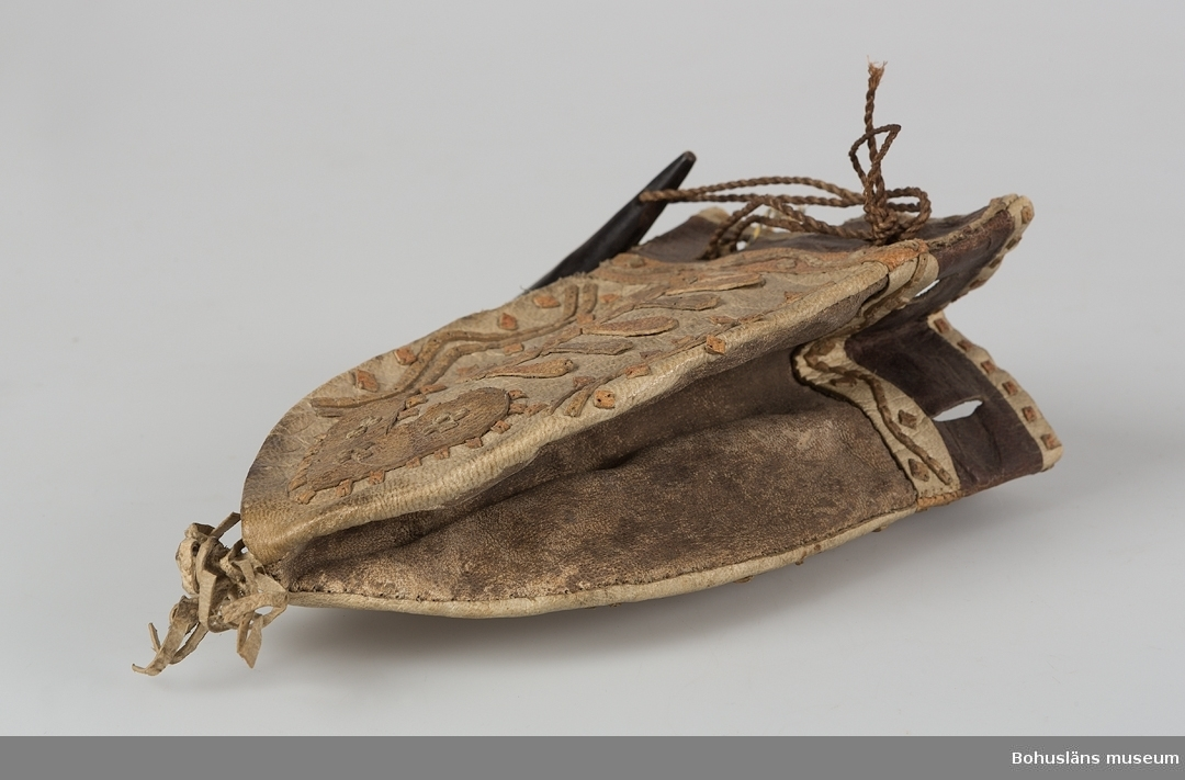Skinnpung med applicerade bitar och band av skinn i mönsterformationer, bland annat hjärta. Liknande mönster på både fram- och baksida. Bruna infällda sidstycken. Drages samman med hjälp av snörning. Till pungen hör ett litet mått med lock. Måttet är gjort av yttersta spetsen av ett horn från ett djur, locket är troligen tillverkat av flätad rot. Enligt en tidigare uppgift ska pungens omkrets upptill vara 40 cm.  Ur handskrivna katalogen 1957-1958: Skinnpung gjord av indian. L. (tofsen oräknad) 19 cm, Br. c:a 10 cm; vitt och brunt skinn, m. applikationer av olikfärgat skinn; upptill snörning. I denna sitter ett horn, b, L. 9,2 cm (ett mått?) med lock av flätverk, c. Pungen något trasig.