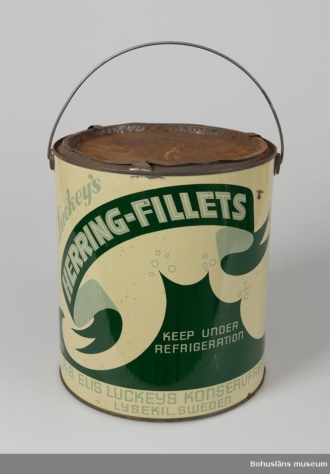 """Grön och vit plåthink/plåtburk med handtag av järntråd. """"Luckeys matjes-filéer Sandelkryddad"""", nu innehållande sandel; krydda som användes vid vissa sillinläggningar. Se UM017232."""