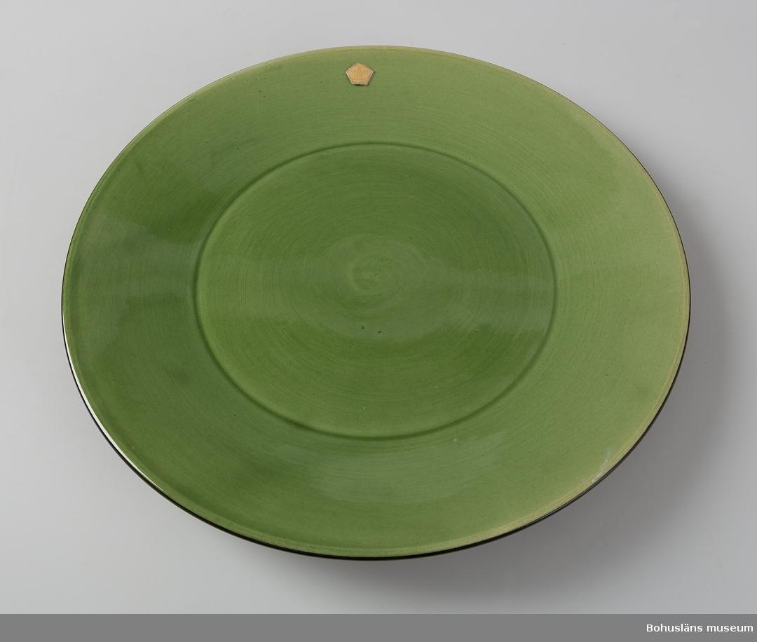 Ovansidan grönglaserad, undersidan svartglaserad. Märkt med påklistrad, delvis avskavt firmamärke.