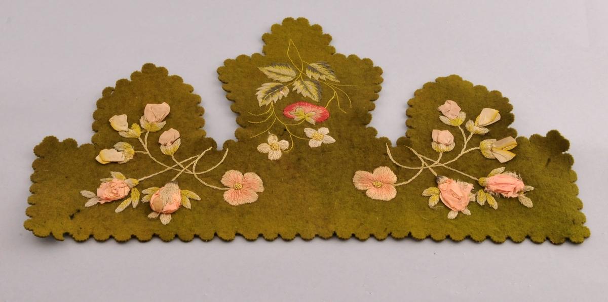 """Stoffstykke i ullstoff med blomstermotiv.Nokre av blomane er brodert med plattsaum, stilkesting,knutar  og sjatterssaum.Andre blomar er laga av tøy. (silke) Kan vera bruka som dekor på ei hylle. Tre """"snippar"""" som heng ned, bølga kant."""
